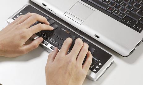 Brailleleesregel die voor een laptop staat.